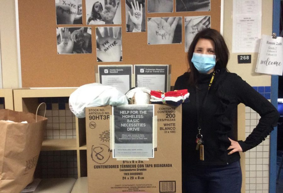 Ms. Fleischer stands beside one of many boxes of donations to Champ Homes. (photo Romy Hoeffgen)